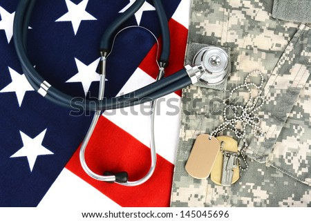 Military fatigues and dog tags on an American Flag with a stethoscope to illustrate health care in the armed services. Horizontal format, fills the frame.