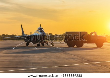 Military fighter is being pushed to a parking lot by a military vehicle at an air base in the evening at sunset #1565869288