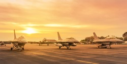 military fighter jet aircrafts parked on runway standby ready to take in sunset