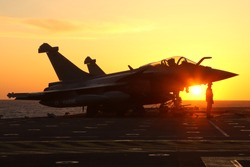 military fighter jet during sunset at aircraft carrier, with silhouette