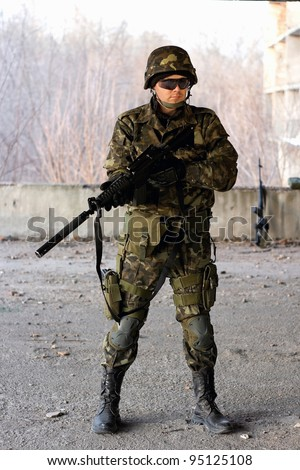 Military guy holding a gun in front of neglected building - stock photo