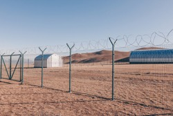 military hangar in the desert behind barbed wire
