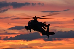 Military helicopter during orange sunset in a lowflying area