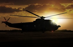 Military helicopter on airfield during sunset