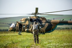 Military helicopter with soldiers. Armed conflict between Israel and Palestine, military action. A soldier in camouflage clothing walks towards a military helicopter. Air armament, parachutist.