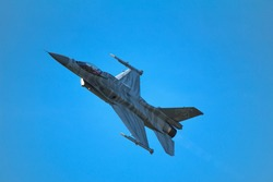 Military jet aircraft dynamic action flight with flairs in blue sky at airshow