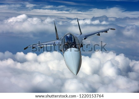 Military jet fighter aircraft flying on a high altitude over the clouds