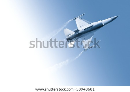 military jet flying through a gradient blue sky