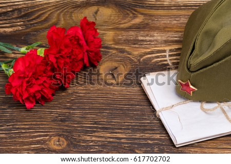 Military letters under the cap and three carnations in honor of May 9 #617702702