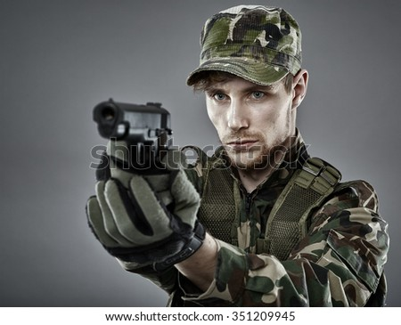 Portrait Of A Young Soldier Aiming And Shooting With A