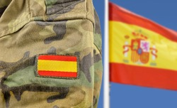Military man posing in front of Spain flag