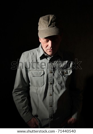 Military man with hands in pocket looking down
