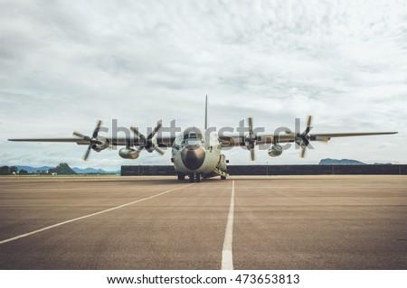 Military men are signaling a C130 military aircraft, propeller aircraft.