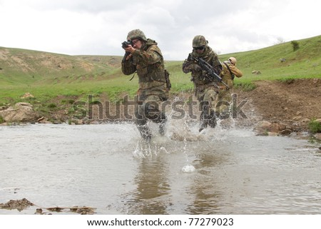 Military men crossing the river under fire