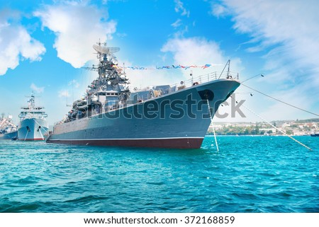 Military navy ship in the bay. Military sea landscape with blue sky and clouds
