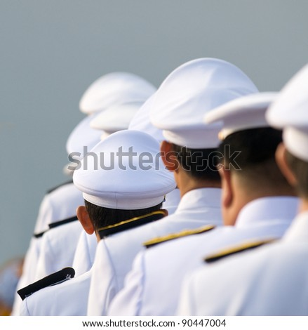 Military officers in parade uniforms seen from behind. Shallow depth of field with the short officers in the middle in focus. Photo taken in Thailand.