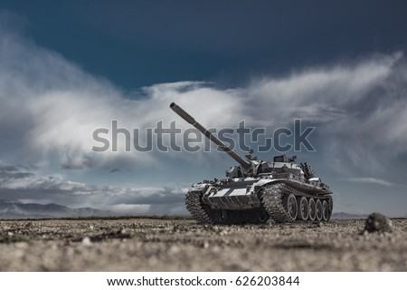 Military or army tank ready to attack and moving over a deserted battle field terrain