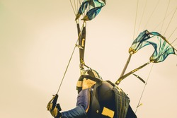Military parachuting, skydiving sports in Thailand ,  Parachuting exit from a helicopter at sunset.
