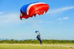 Military parachuting, skydiving sports in Thailand  ,  Parachutist in military uniform walking on the field after the jump with his parachute