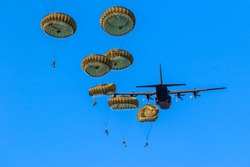 Military parachutist paratroopers parachute jumping out of a air force planes on a clear blue sky day.