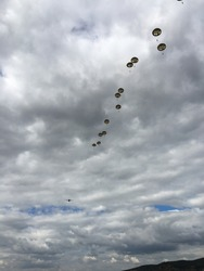 Military parachutists descending using automatic round canopy parchutes