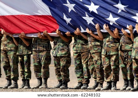 military personnel holding large American Flag