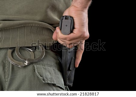 Military police officer holding hand on a gun in a holster.