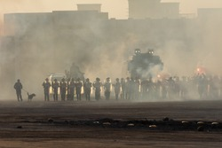 Military police riot line up response to a protest with tear gas, smoke, fire, explosions and police dogs. Political expression, riot, protest, demostration and military concept.