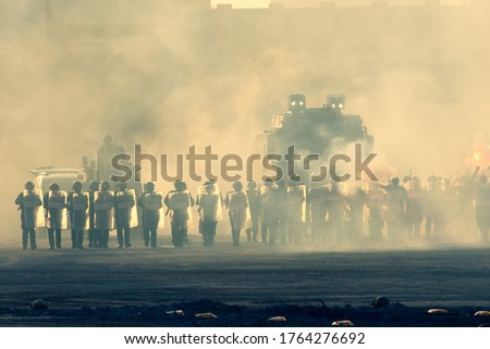 Military police riot response to a protest with tear gas, smoke, fire, explosions. Political expression, riot, protest, demostration and military concept.