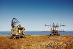 Military radar and locator on the car. Abandoned equipment on the background of the autumn landscape, sea and blue sky