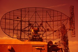 Military radar on the roof of a military vehicle. Military locator on a bright sky background