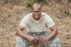 Military soldier relaxing during obstacle training at boot camp
