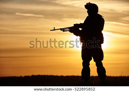 Military soldier silhouette with machine gun