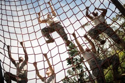 Military soldiers climbing rope during obstacle course in boot camp