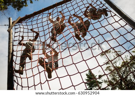 Military soldiers climbing rope during obstacle course in boot camp Foto d'archivio ©