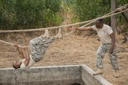 Military soldiers climbing rope during obstacle course training at boot camp