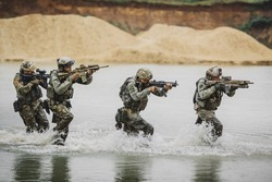 Military squad crossing the river under fire