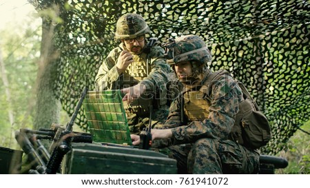 Military Staging Base, Chief Engineer Uses Radio and Army Grade Laptop. Forest Operation/ Mission in Progress. #761941072