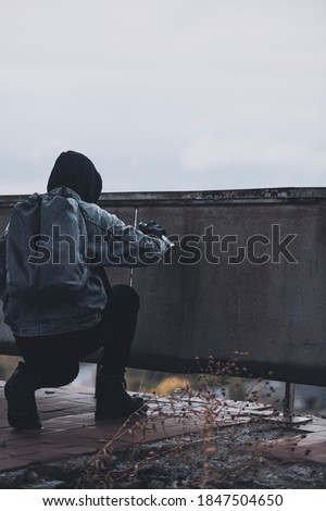 Military styled man starts to paint something on the wall with spray paint stock photo