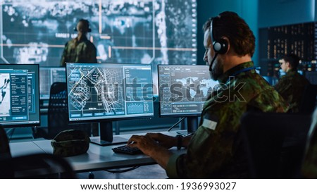 Military Surveillance Officer Working on a City Tracking Operation in a Central Office Hub for Cyber Control and Monitoring for Managing National Security, Technology and Army Communications.