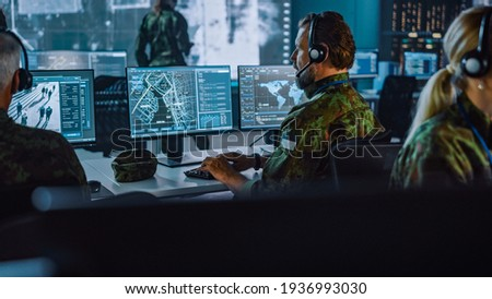 Military Surveillance Officer Working on a City Tracking Operation in a Central Office Hub for Cyber Control and Monitoring for Managing National Security, Technology and Army Communications. Photo stock ©