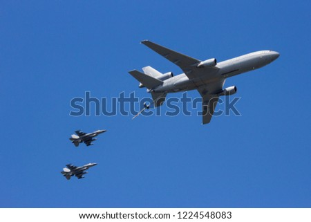 Military tanker plane aerial refueling two fighter jet aircraft.