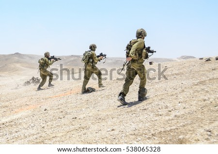 MILITARY TRAINING ZONE, ISRAEL - JUNE 17, 2015: Israeli army combat soldiers firing while charging terror targets. Infantry commando troops storming & shooting during military training in the desert. - Shutterstock ID 538065328
