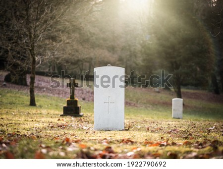 Military white British World War One grave with no inscription unknown soldier alone with sun rays shining peaceful and tranquil down through trees from 1914 to 1918 in cemetery church graveyard ww1 Stockfoto ©