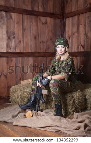 Military women with a weapon. Military women rest on straw