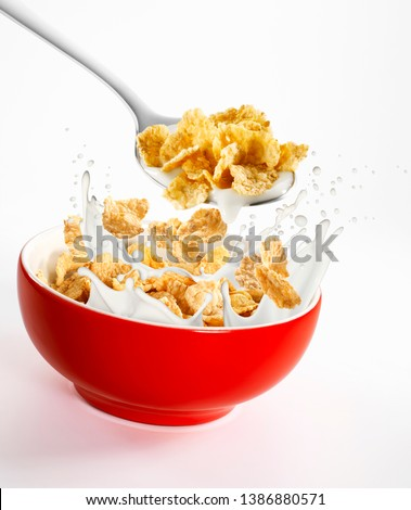 Milk and cornflakes splash, in a red bowl and a spoon with milk and cornflakes on a white background #1386880571