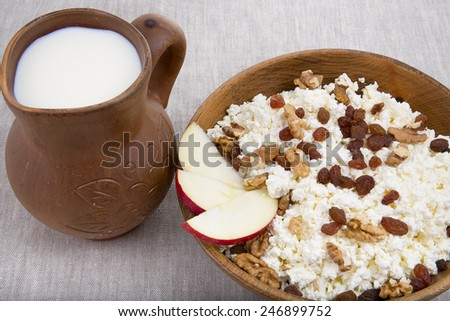 milk and cottage cheese with raisins, nuts and apple in a clay pot natural