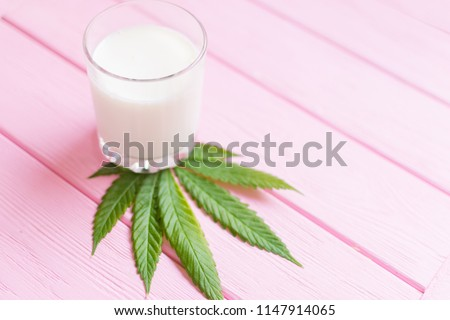 Milk and hemp. A glass of milk on a sheet of marijuana on a pink wooden background.