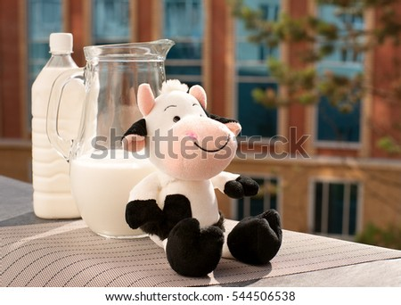 Milk and toy cow. Funny spotted cow against a background of milk. Milk in a jug and a plastic bottle on the windowsill balcony. Breakfast is good for health. #544506538