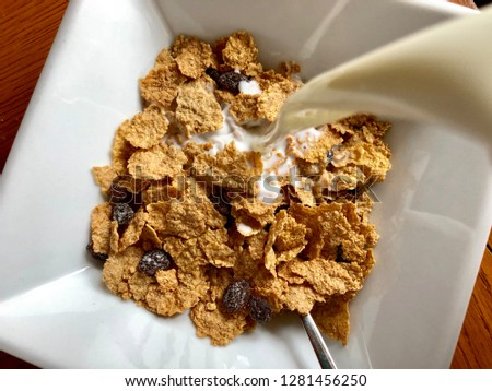 Milk poured into bowl of bran cereal Free Images and Photos
